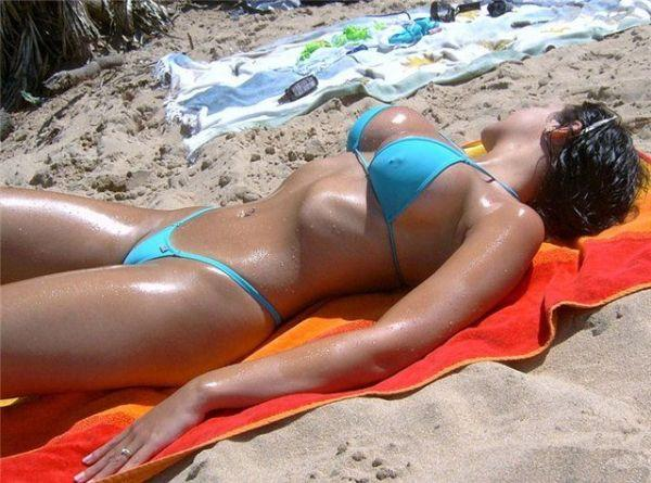 Oily tanned mistress with tiny swimsuit alone at the beach