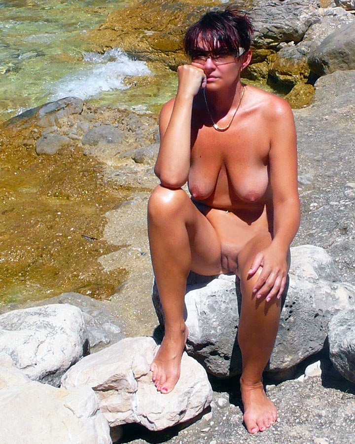 Woman sitting naked in the outdoors under the sun