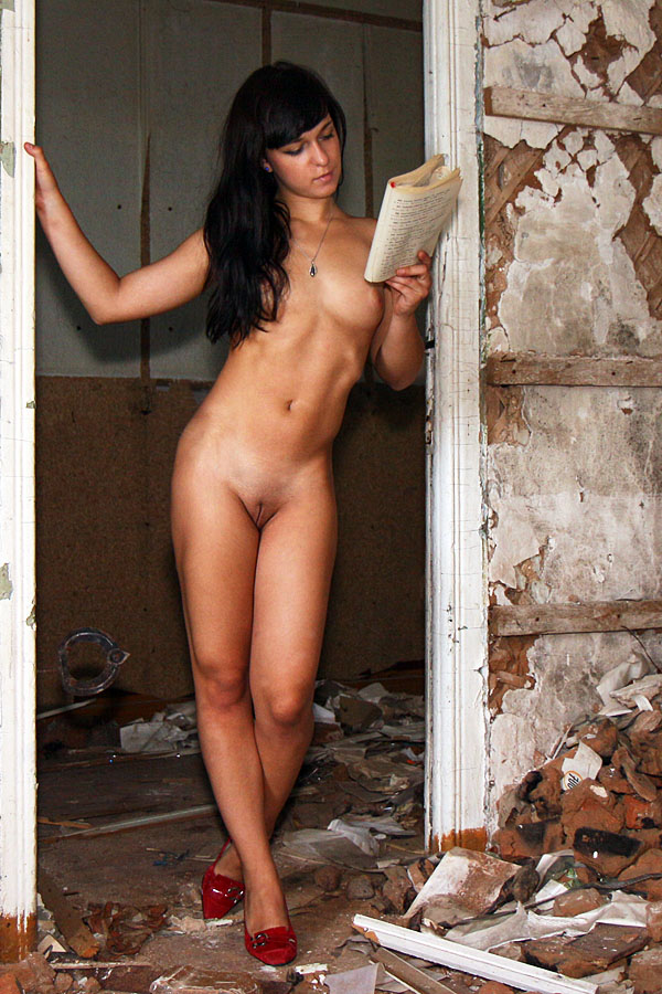 Nude woman reading a book in a broken down house